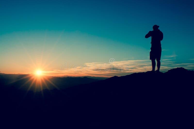 La silueta del hombre en la puesta del sol imagenes de archivo