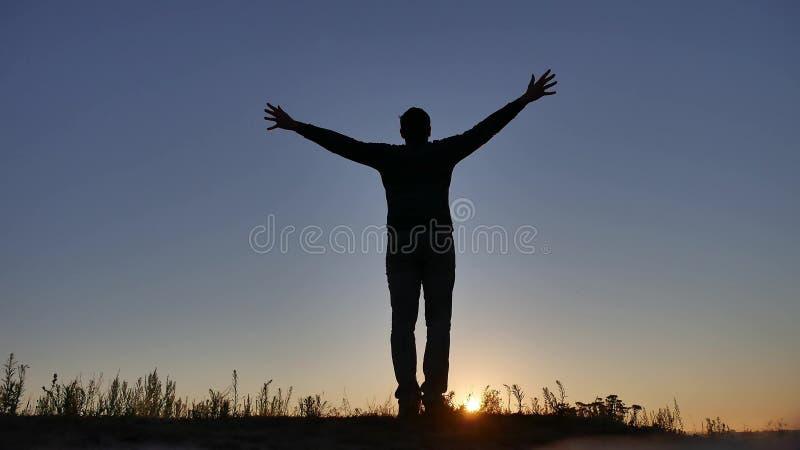 La silueta del hombre se separó las manos a los lados Alegría de la libertad del hombre del viaje fotos de archivo libres de regalías