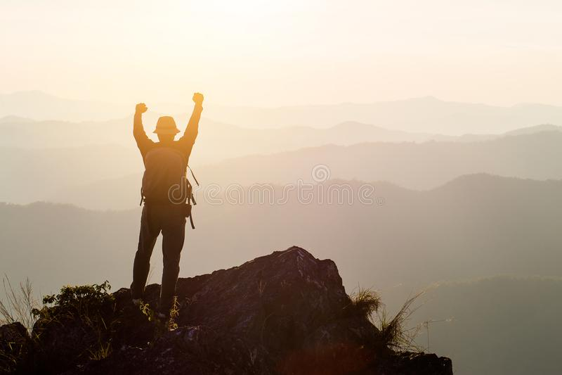 La silueta del hombre soporta las manos en el pico de la montaña, concepto del éxito imagen de archivo
