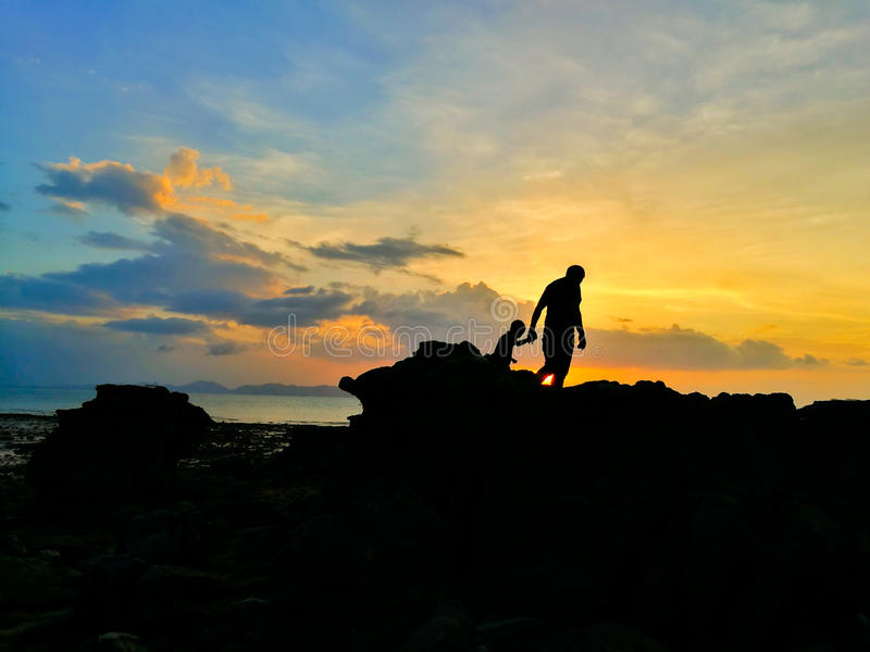 La silueta del padre y del hijo cariñosos caminó en la playa y el beauti imagen de archivo