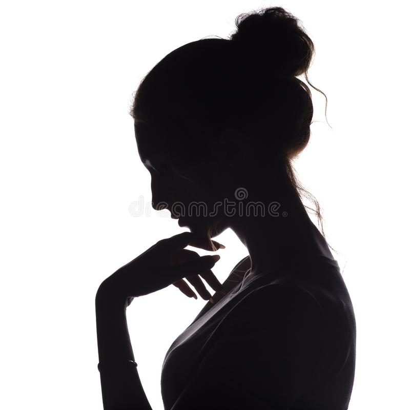 La silueta del perfil de una muchacha pensativa con una mano en la barbilla, una mujer joven bajó su cabeza abajo en un fondo ais imágenes de archivo libres de regalías