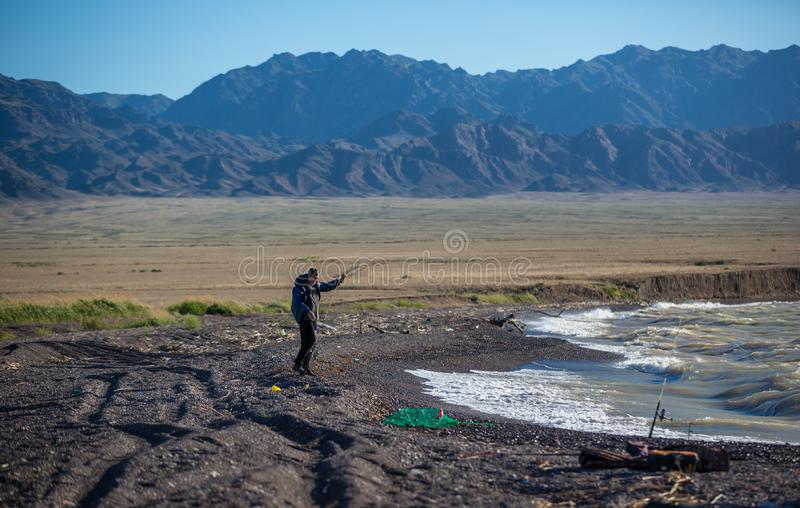 La silueta del pescador en la línea del control del pescador de la puesta del sol y el cebo el empujar en la barra, se preparan y foto de archivo