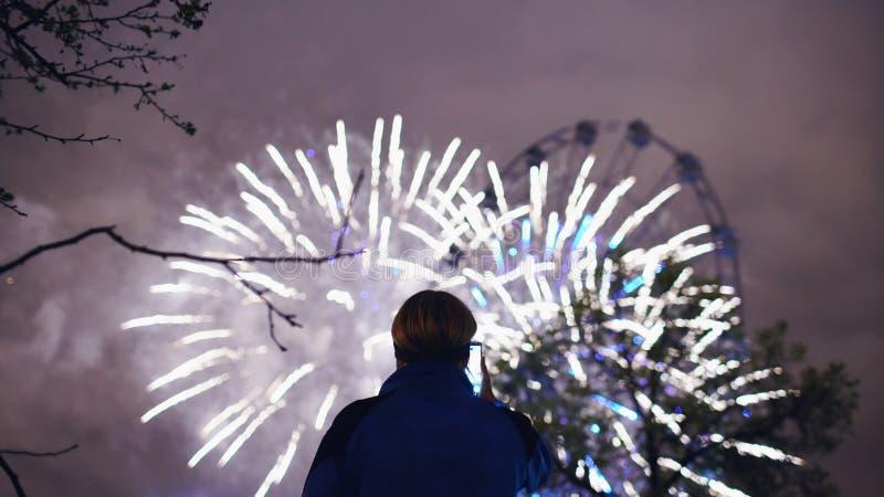 La silueta del primer del hombre que mira y que fotografía los fuegos artificiales estalla en cámara del smartphone al aire libre fotos de archivo