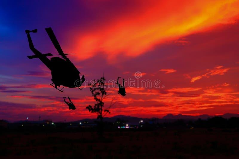 La silueta del soldado en rappelling sube abajo del helicóptero en la puesta del sol, guerra de la parada del concepto con el esp fotografía de archivo