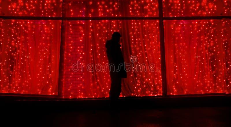 La silueta en la noche contra la perspectiva de las guirnaldas, una persona se coloca en la calle Concepto del Año Nuevo foto de archivo libre de regalías