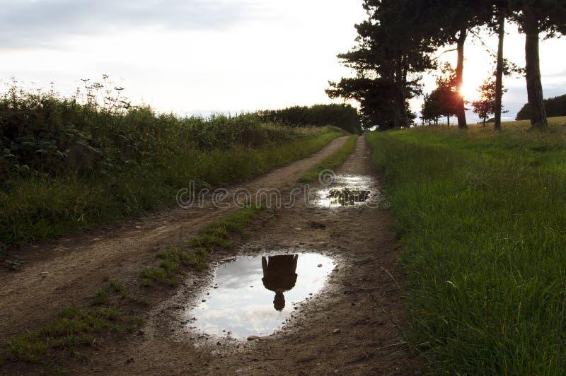 La silueta fantasmal de una persona que no está allí, reflejó en un charco en una trayectoria del país en la puesta del sol fotografía de archivo libre de regalías