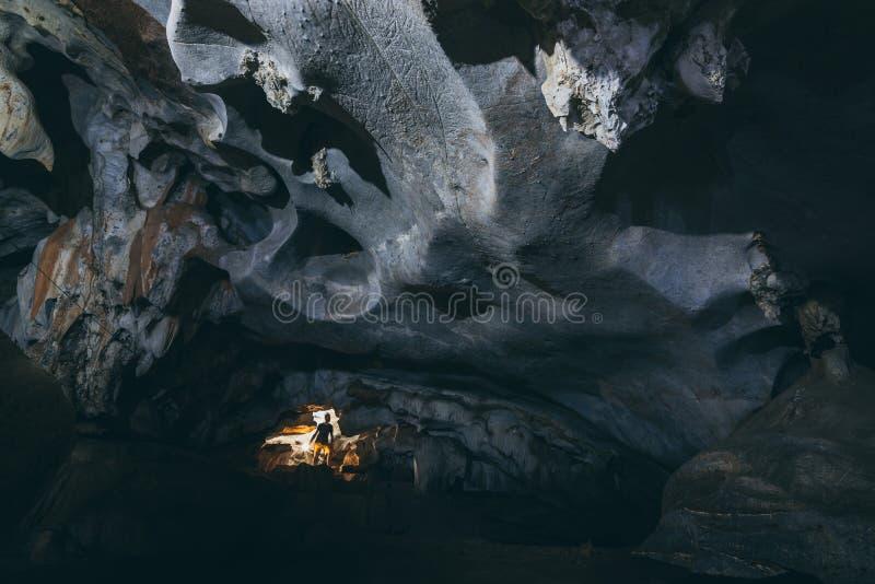 La silueta humana se coloca dentro de la cueva con la luz que viene del techo imagen de archivo libre de regalías