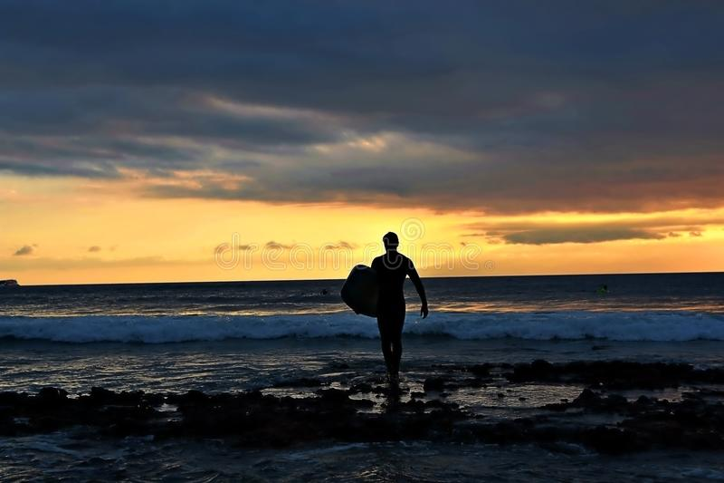 La silueta ocen a la persona que practica surf imagen de archivo libre de regalías