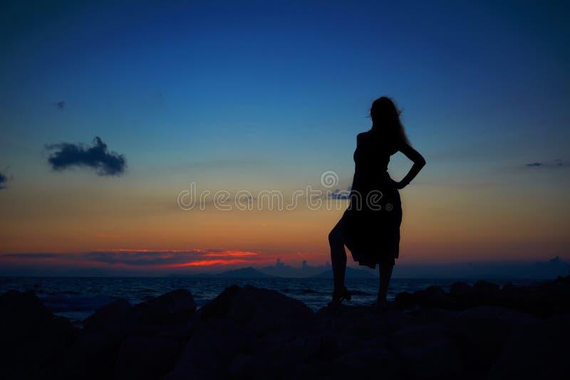 La silueta romántica de la mujer bonita joven hermosa en puesta del sol emite en la playa del arena de mar y de la piedra Mujer m imagenes de archivo