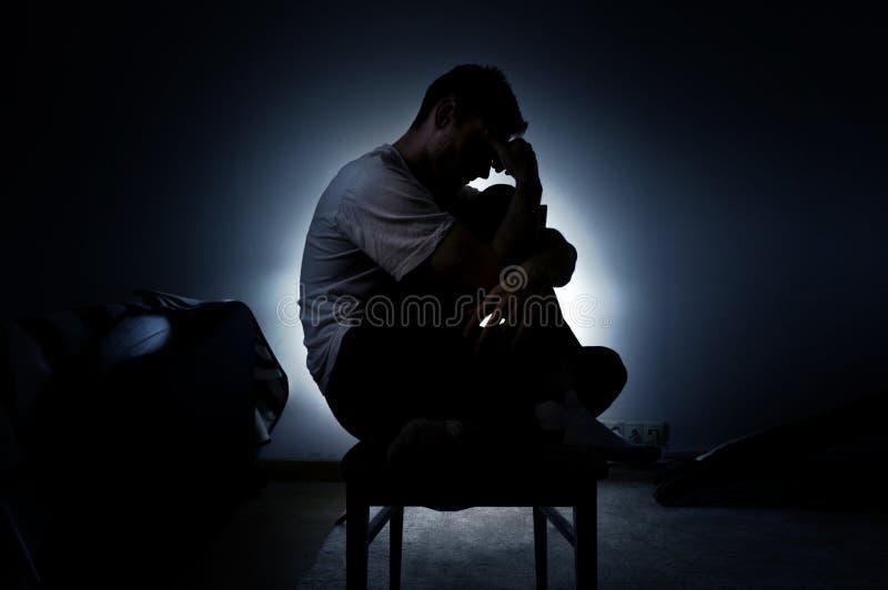 La silueta triste de un hombre en la depresión que se sienta en una silla con su cabeza abajo, piensa en vida fotografía de archivo libre de regalías