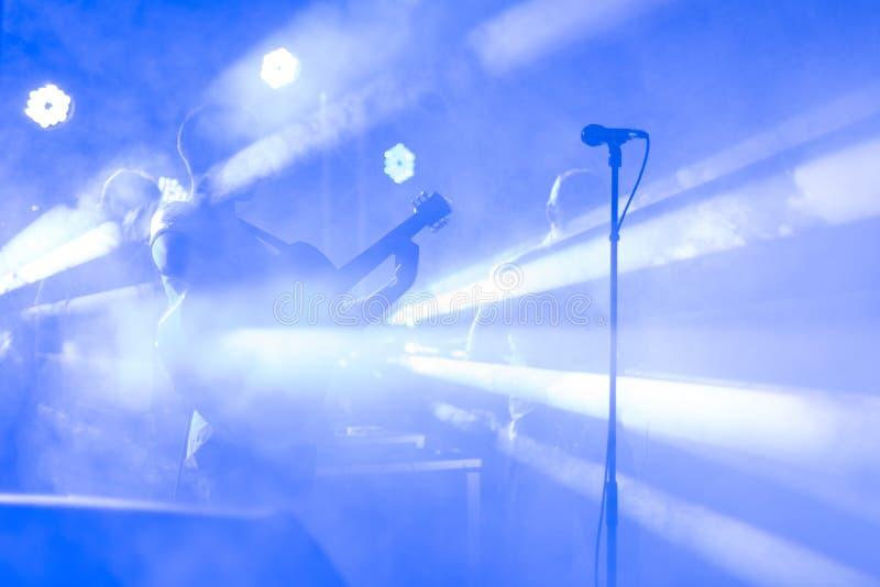 La siluetta del chitarrista esegue su una fase di concerto Priorità bassa musicale astratta Banda di musica con il giocatore di c fotografia stock libera da diritti