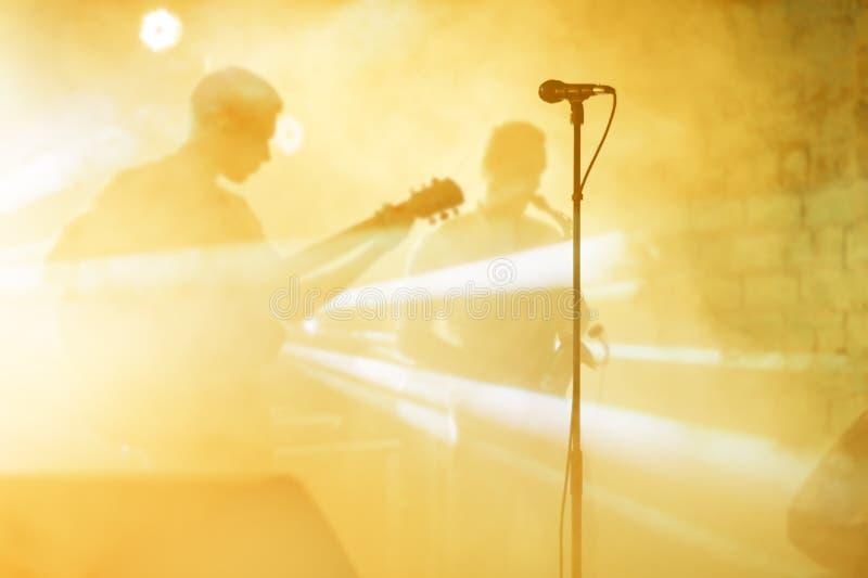 La siluetta del chitarrista esegue su una fase di concerto Priorità bassa musicale astratta Banda di musica con il giocatore di c fotografie stock