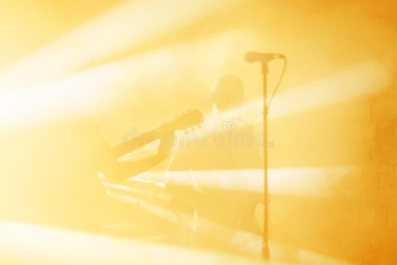 La siluetta del chitarrista esegue su una fase di concerto Priorità bassa musicale astratta Banda di musica con il giocatore di c fotografie stock libere da diritti