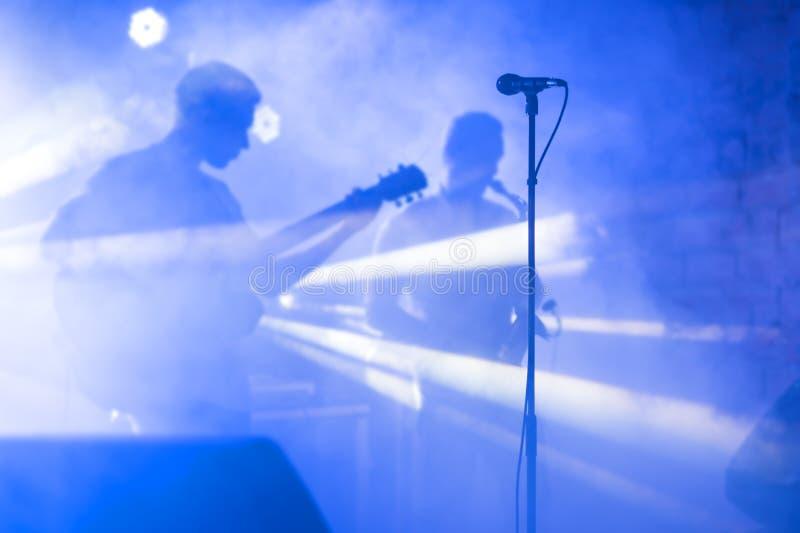 La siluetta del chitarrista esegue su una fase di concerto Priorità bassa musicale astratta Banda di musica con il giocatore di c immagini stock