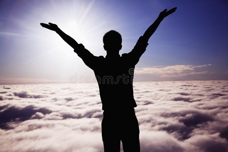La siluetta del giovane con le armi si è alzata con le nuvole ed il cielo nei precedenti fotografie stock libere da diritti