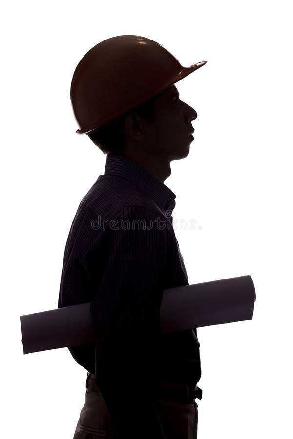 La siluetta del muratore con il progetto in mani, uomo in camici in casco ed occhiali di protezione su bianco ha isolato il backg fotografia stock