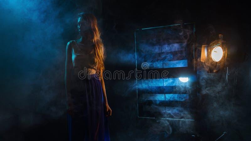 La siluetta del ` s della ragazza in nebbia contro lo sfondo del sou leggero fotografie stock