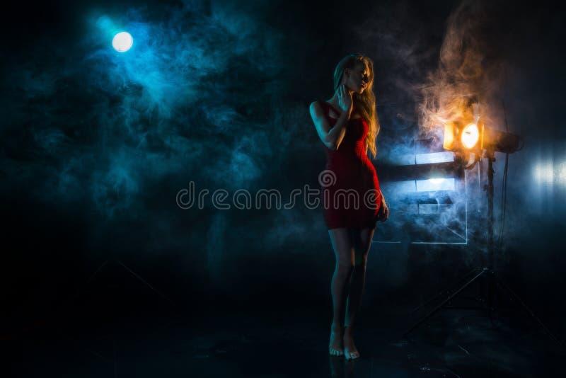 La siluetta del ` s della ragazza in nebbia contro lo sfondo del sou leggero fotografia stock