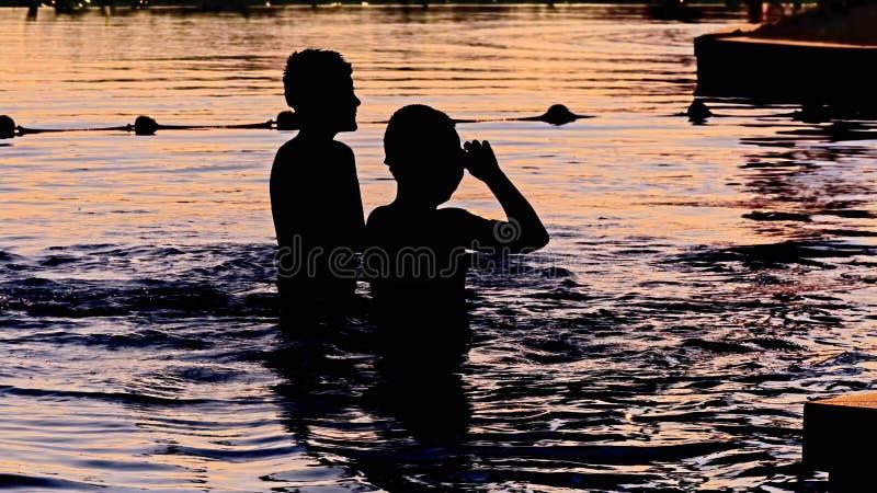 La siluetta del tramonto dei bambini felici gode dei giochi dell'acqua nella cacca fotografie stock