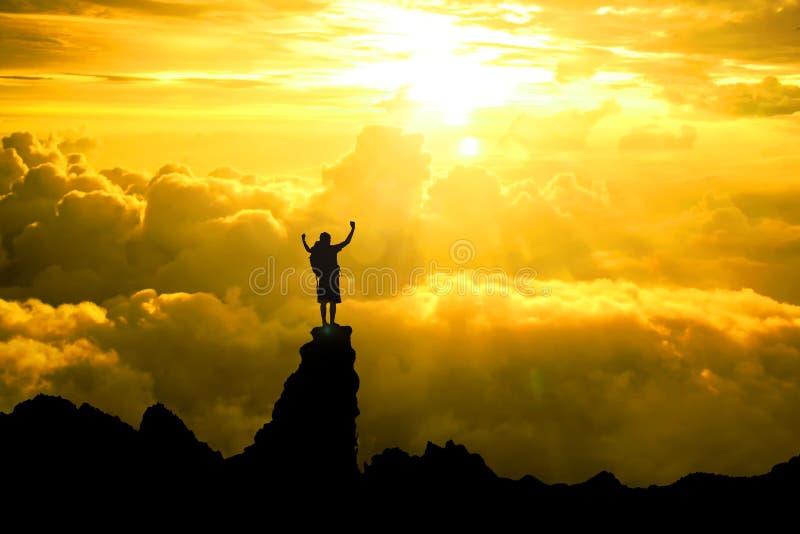 La siluetta del viaggiatore con zaino e sacco a pelo degli uomini a braccia aperte si è alzata verso su speranza SK fotografie stock