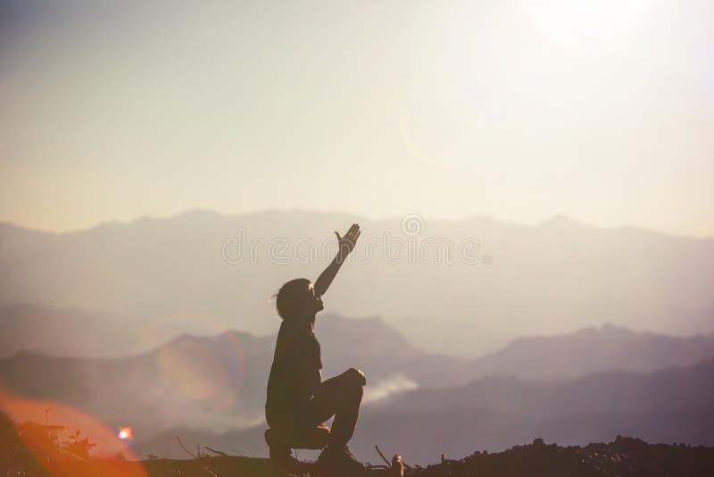 La siluetta dell'uomo che prega esterno fotografia stock libera da diritti