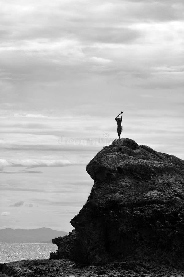 La siluetta dell'uomo del Fijian sta su una scogliera del mare in Figi immagini stock