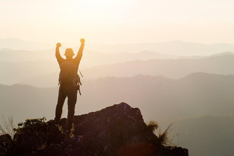 La siluetta dell'uomo ostacola le mani sul picco della montagna, concetto di successo immagine stock