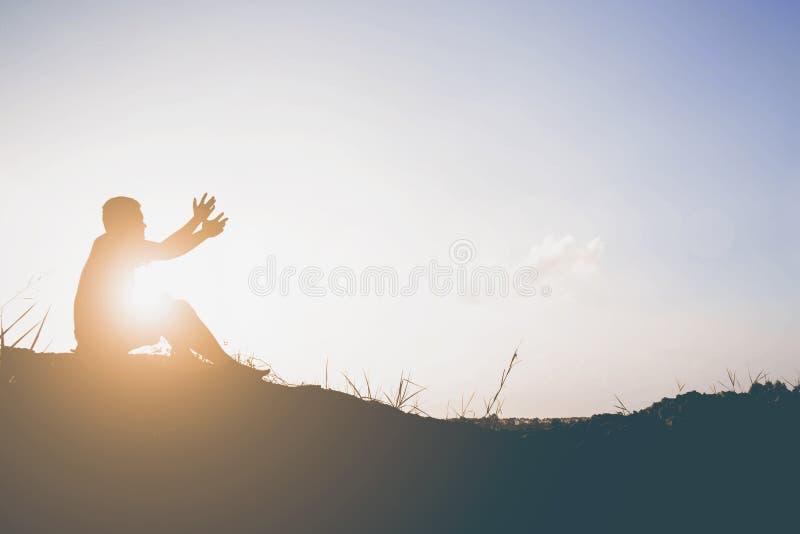 La siluetta dell'uomo prega là è speranza fotografia stock libera da diritti