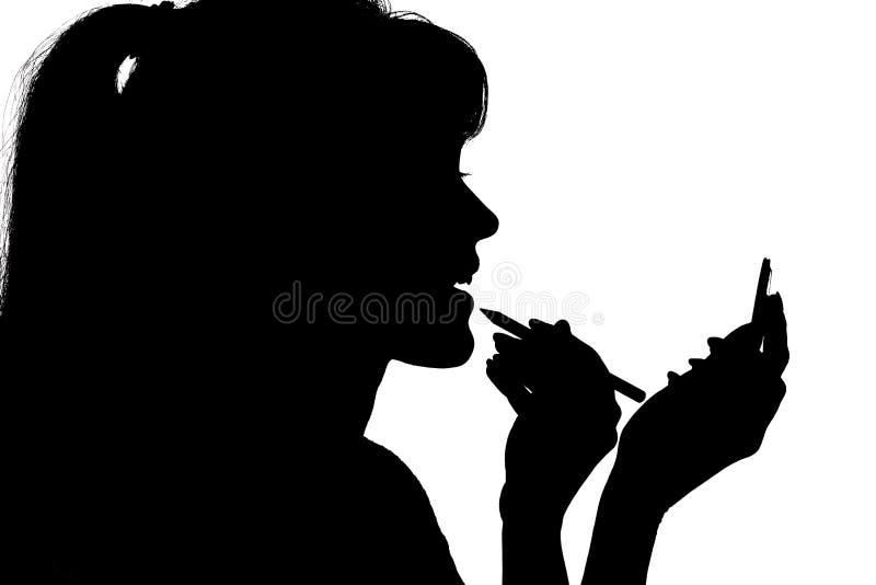 La siluetta della donna che fa il trucco davanti allo specchietto in mani su bianco ha isolato il fondo fotografia stock libera da diritti