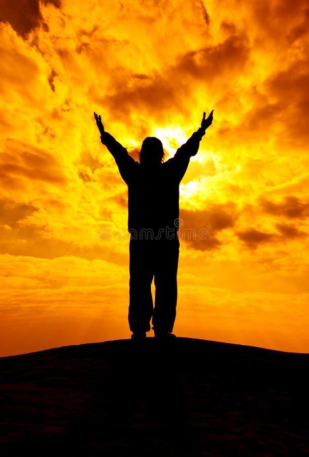 La siluetta della donna con le mani aumenta su e prega con luce solare f fotografia stock libera da diritti