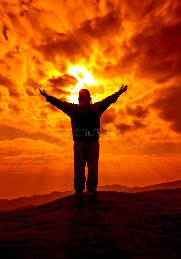 La siluetta della donna con le mani aumenta su e prega con luce solare f immagine stock libera da diritti