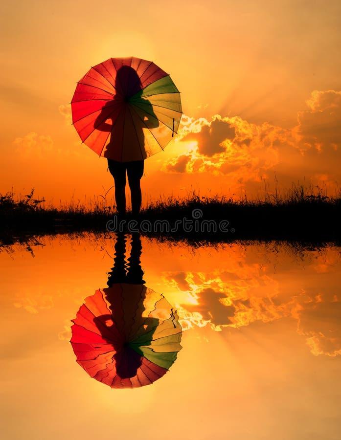 La siluetta della donna e di tramonto dell'ombrello, l'acqua riflette fotografia stock libera da diritti