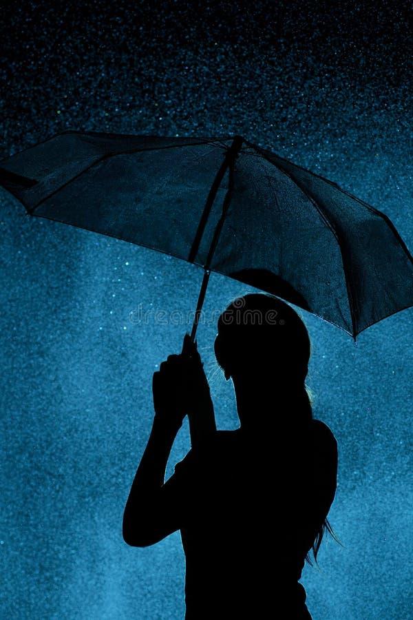 La siluetta della figura di una ragazza con un ombrello nella pioggia, una giovane donna è felice alle gocce dell'acqua, tempo di immagini stock