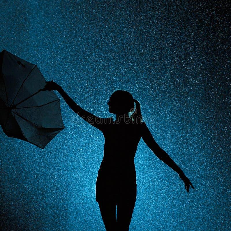 La siluetta della figura di una ragazza con un ombrello nella pioggia, una giovane donna è felice alle gocce dell'acqua, tempo di fotografia stock