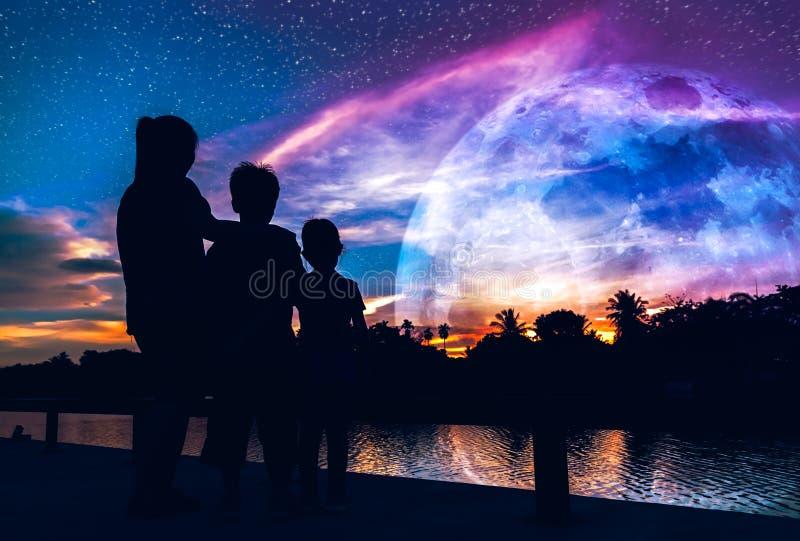 La siluetta della madre con il figlio e la figlia che gode della vista a rive immagini stock libere da diritti