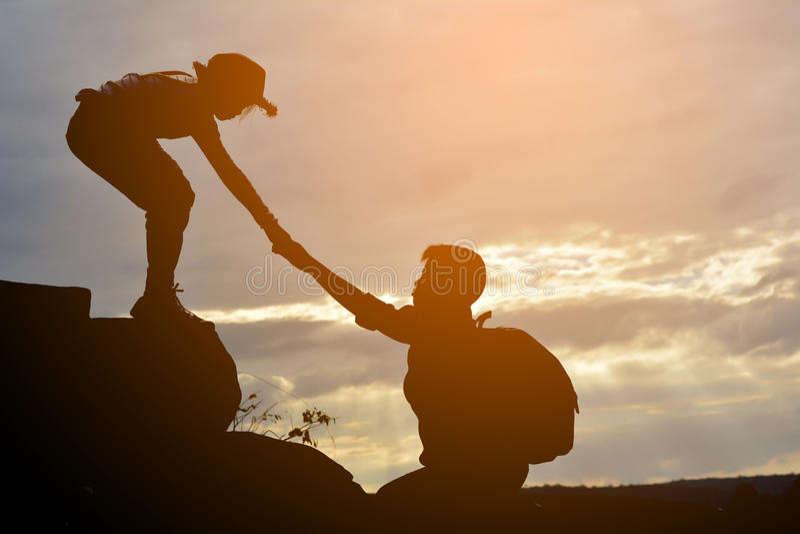La siluetta della ragazza aiuta un ragazzo sulla montagna fotografia stock