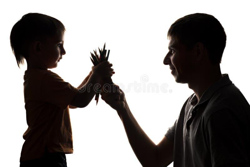 La siluetta delle relazioni di famiglia, il padre dà la matita di colore del bambino immagine stock