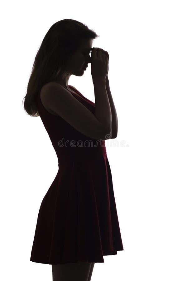 La siluetta di profilo di giovane donna turbata, la ragazza pende la sua mano sulla sua fronte e pensa ai problemi, il concetto d immagine stock libera da diritti