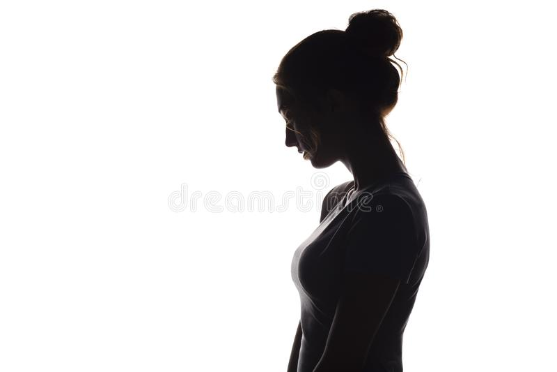 La siluetta di profilo di una ragazza pensierosa, una giovane donna ha abbassato la sua testa giù su un fondo isolato bianco immagine stock