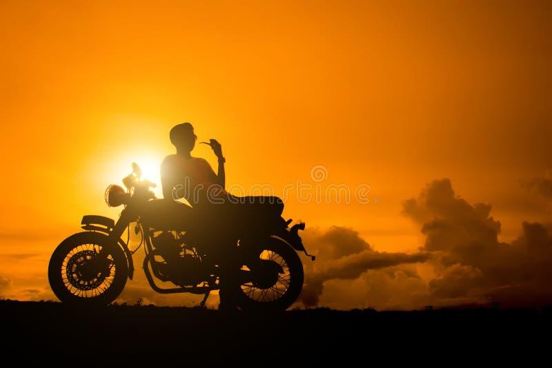 La siluetta di seduta dell'uomo del motociclista fuma con la sua motocicletta accanto al lago naturale e bello, godendo della lib immagine stock