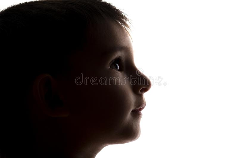 La siluetta di un fronte del bambino piccolo che guarda verso l'alto, bambini dirige il profilo fotografia stock