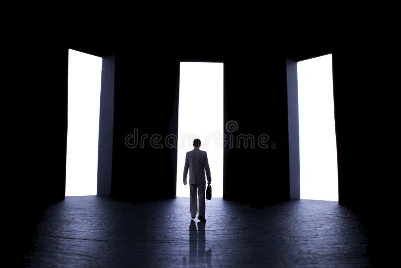 La siluetta di un giovane in un vestito con una cartella davanti a tre porte aperte, persona decide che percorso da scegliere, immagini stock