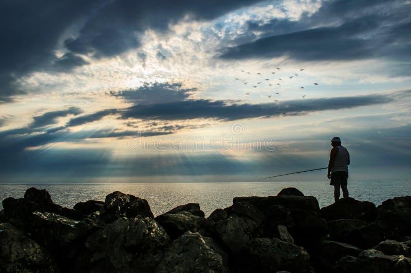 La siluetta di un pescatore, da pesca fuori dalla riva dell'oceano all'alba un bello cielo in pieno delle nuvole e dei raggi del  fotografie stock