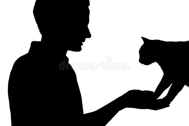 La siluetta di un ragazzo con un gatto, uomo che esamina l'animale domestico su bianco ha isolato il fondo fotografia stock