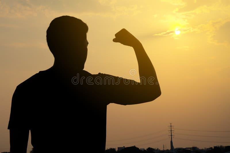La siluetta di un uomo, i suoi muscoli di armi mostra forte fotografie stock libere da diritti
