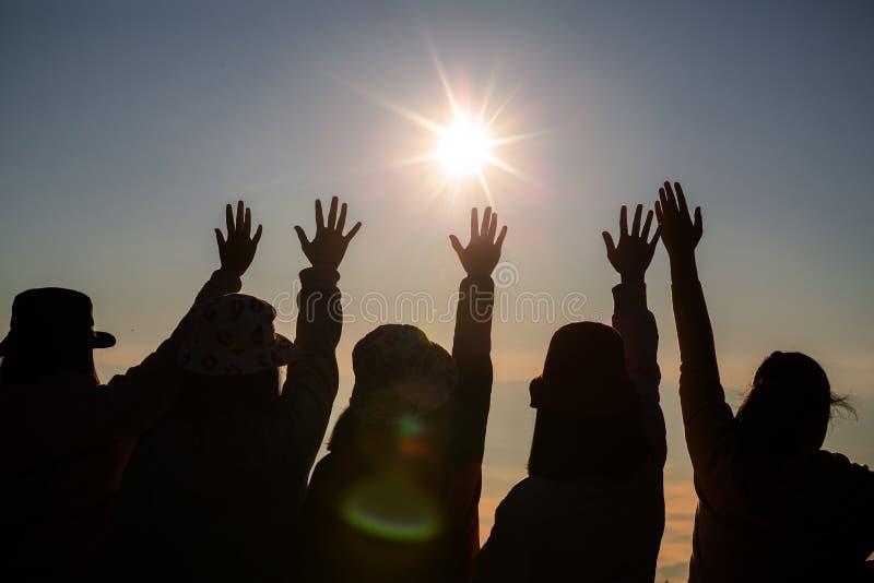 La siluetta di una giovane donna sta stando sulla cima di una montagna che si rilassa dal sole all'alba dall'alba fotografie stock libere da diritti