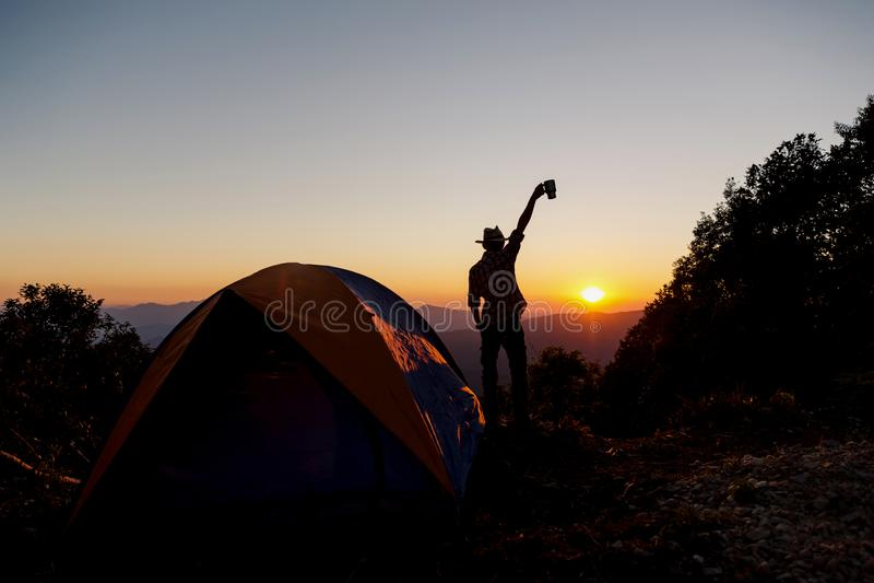 La siluetta di una persona è soddisfatta della tenuta un la tazza di caffè vicino alla tenda intorno alla montagna fotografia stock