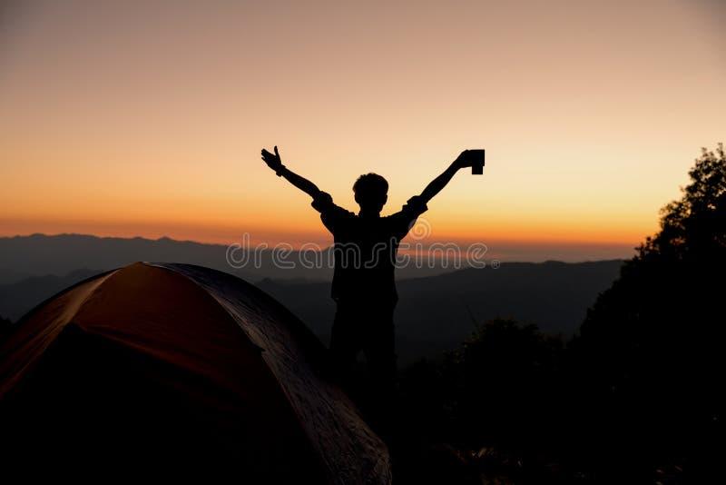 La siluetta di una persona ? soddisfatta della tenuta un la tazza di caff? vicino alla tenda intorno alla montagna immagini stock