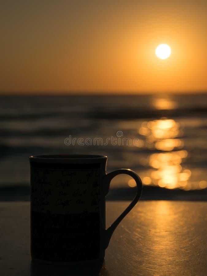 La siluetta di una tazza sulla tavola ed i precedenti di alba al lungonmare fotografia stock