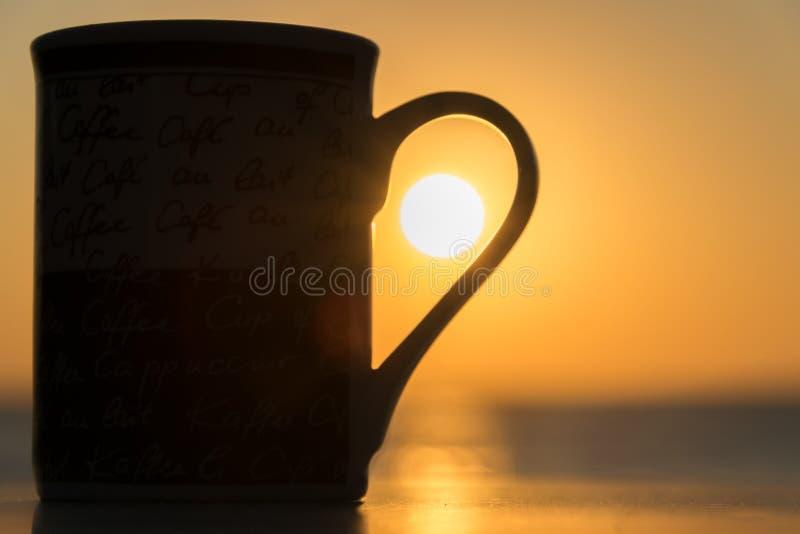 La siluetta di una tazza sulla tavola ed i precedenti di alba al lungonmare fotografia stock libera da diritti